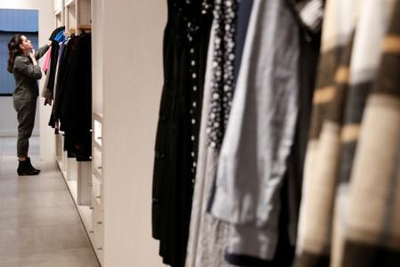 A woman looks at clothes at the Rent The Runway store, an online subscription service for women to rent designer dress and accessory items, in New York City