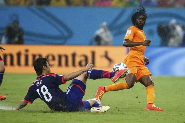Japan's Yuya Osako (L) fights for the ball with Ivory Coast's Gervinho during their 2014 World Cup Group C soccer match at the Pernambuco arena in Recife June 14, 2014. REUTERS/Yves Herman (BRAZIL - Tags: SOCCER SPORT WORLD CUP)
