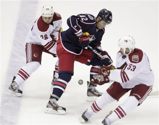 Columbus Blue Jackets' Artem Anisimov, center, of Russia, carries the puck between Phoenix Coyotes' Steve Sullivan, left, and Derek Morris during overtime in an NHL hockey game Saturday, March 16, 2013, in Columbus, Ohio. The Blue Jackets beat the Coyotes 1-0 in a shootout. (AP Photo/Jay LaPrete)