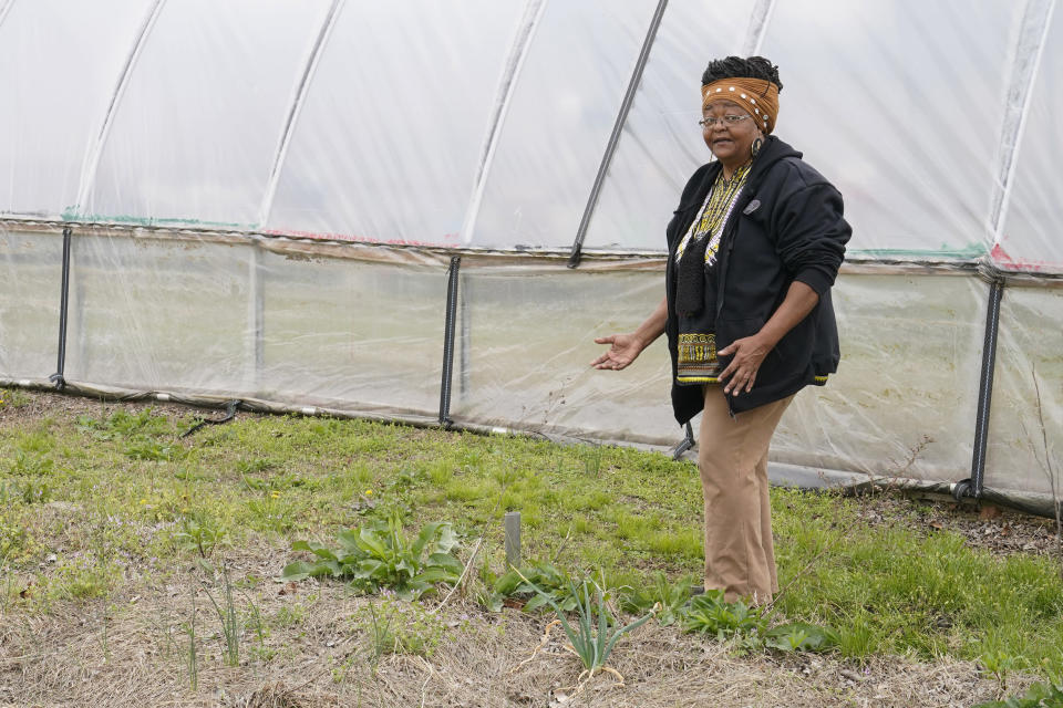 Billie Parker, owner of the Black Wall Street Market, walks through her garden area in Tulsa, Okla., on Saturday, April 10, 2021. The 6 miles between the old and new incarnations of Black Wall Street belie the dire connection that links them: Racial and socioeconomic inequality on Tulsa's north side has its roots in the 100-year-old atrocity of the Tulsa Race Massacre. (AP Photo/Sue Ogrocki)