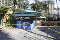 An entrance to a popular resort in Waikiki is closed off to the public Thursday, Oct. 15, 2020, in Honolulu. A new pre-travel testing program will allow visitors who test negative for COVID-19 to come to Hawaii and avoid two weeks of mandatory quarantine goes into effect Thursday. The pandemic has caused a devastating downturn on Hawaii's tourism-based economy and many are hoping the testing will help the economy rebound. (AP Photo/Marco Garcia)