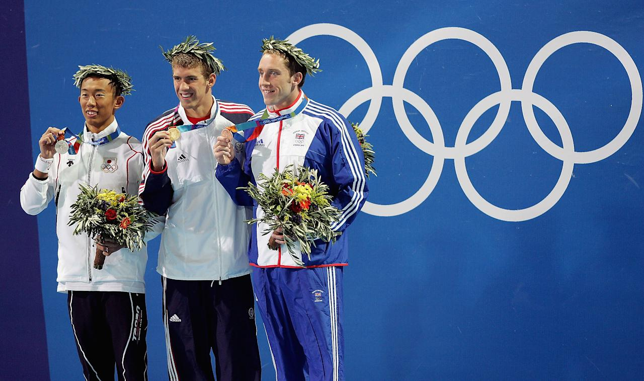 ATHENS - AUGUST 17:  (L-R) Takashi Yamaoto of Japan, Michael Phelps of USA and Stephen Parry of Great Britain pose with their medals for the men's swimming 200 metre butterfly event on August 17, 2004 during the Athens 2004 Summer Olympic Games at the Main Pool of the Olympic Sports Complex Aquatic Centre in Athens, Greece. (Photo by Stuart Franklin/Getty Images)