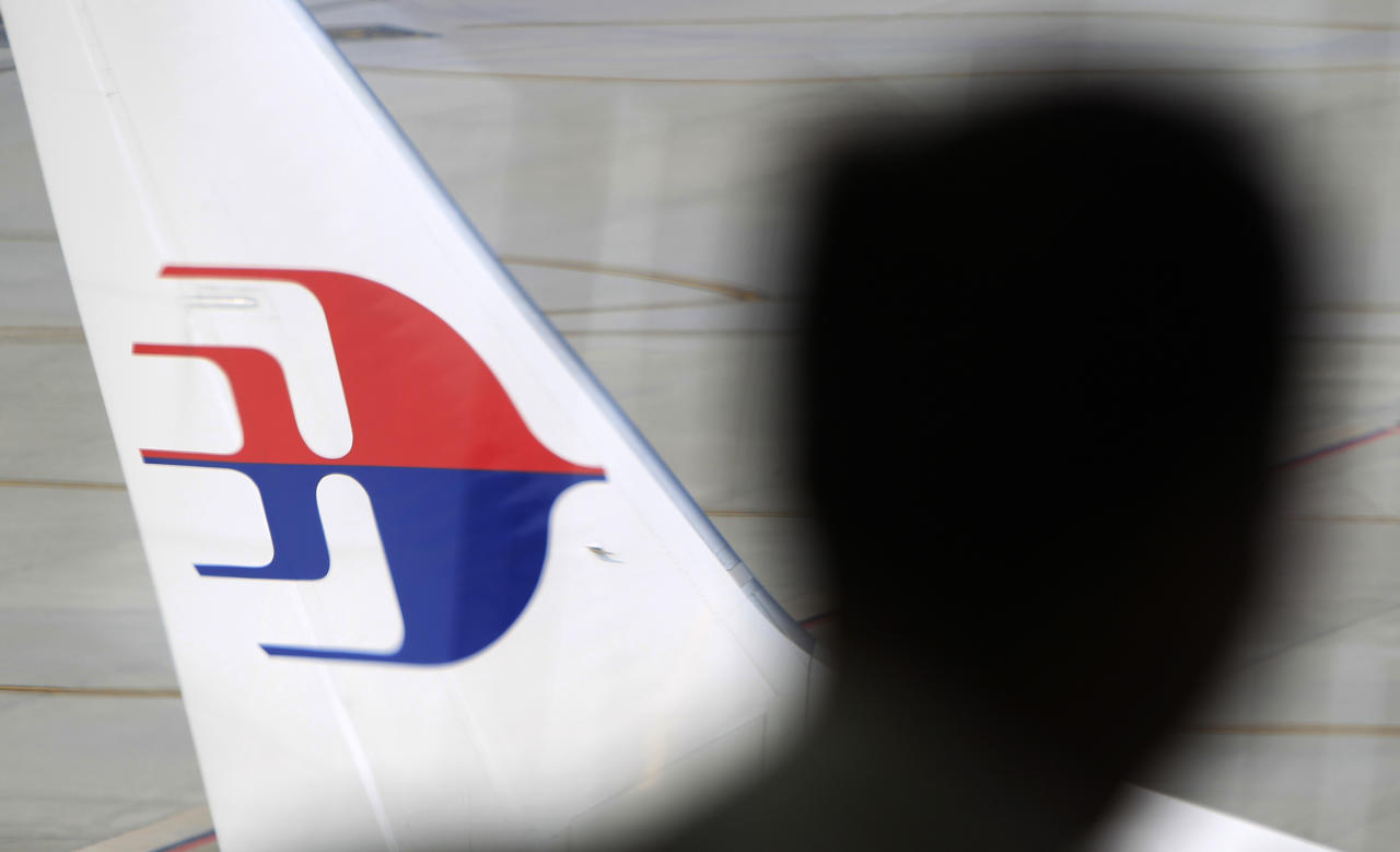 FILE - In this Sunday, March 9, 2014, file photo, a man looks out from a viewing gallery as a Malaysia Airlines aircraft sits on the tarmac at Kuala Lumpur International Airport in Sepang, Malaysia. A photo has been sent to prosecutors anonymously, purporting to show the actual Buk rocket on a launcher that blew the Malaysia Airlines Flight 17 passenger jet out of the sky in 2014, killing all 298 on board, and now prosecutors have appealed Thursday Oct. 19, 2017, for information about the photograph. (AP Photo/Lai Seng Sin, File)