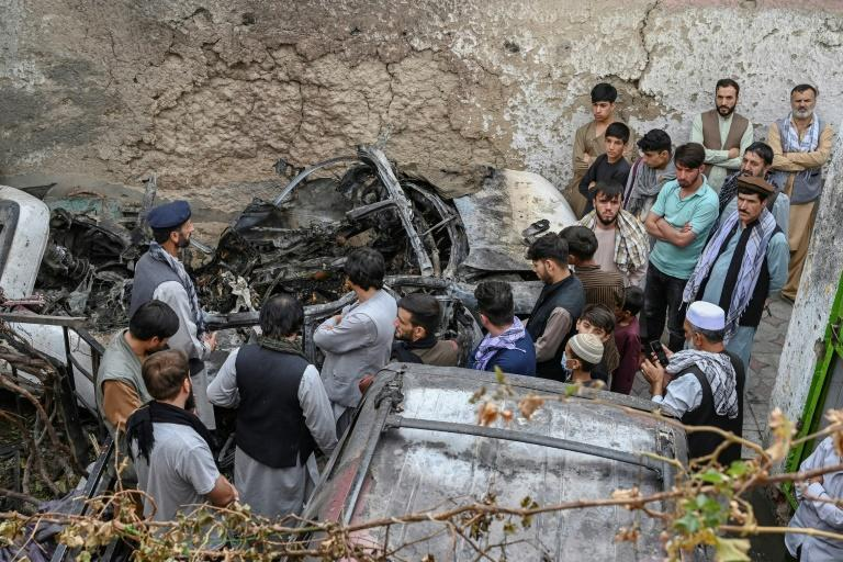 Kabul residents and family members gather next to a damaged vehicle a day after a US drone airstrike that killed 10 civilians (AFP/WAKIL KOHSAR)