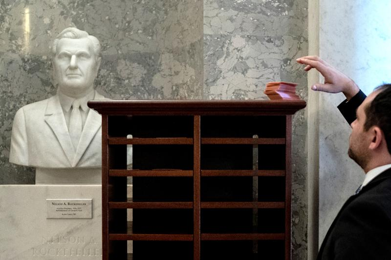 A Capitol employee sets up numbered cubbies to store lawmakers' phones at the Capitol in Washington on Thursday, Jan. 16, 2020, if they come to attend the Senate impeachment trial. (Erin Schaff/The New York Times)