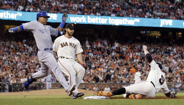 San Francisco Giants' Brandon Belt slides into first to force out Kansas City Royals' Salvador Perez during the fourth inning of Game 5 of baseball's World Series Sunday, Oct. 26, 2014, in San Francisco. (AP Photo/David J. Phillip)
