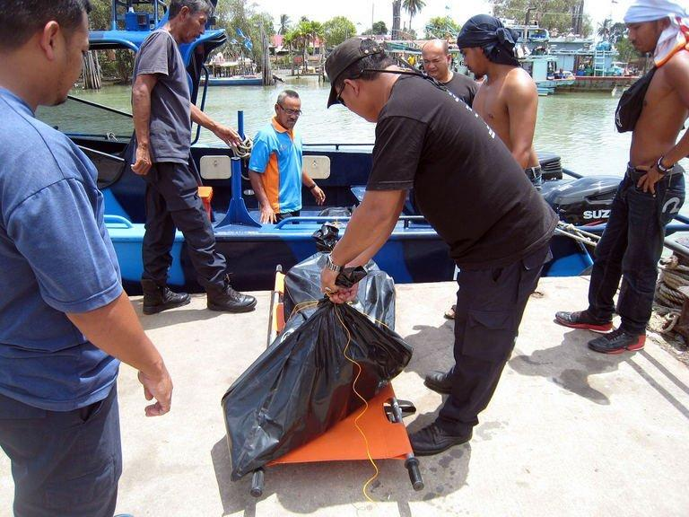 This photo, taken on August 4, 2013, and released by the Malaysian Maritime Enforcement Agency, shows officials at the Maritime office in Tanjung Sedili in Johor state transporting three victims found at sea after a wooden boat that was believed to be carrying 44 people, sank off the coast