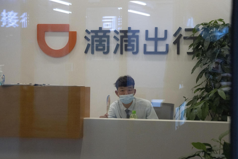 FILE - In this July 16, 2021, file photo, a receptionist looks up from an office for drivers of Didi in Beijing. Foreign shareholders in China's tech companies are learning what its entrepreneurs have long known: The ruling Communist Party's decisions about what is good for the economy can hurt your business. (AP Photo/Ng Han Guan, File)