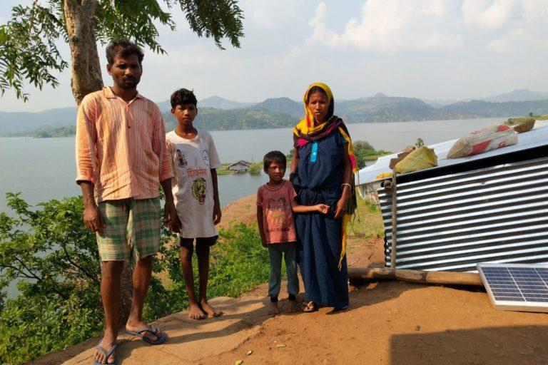 Ozabai and Divalya Vasave along with their kids in Bamani Village. The tin shed is their home right across the submerged one. Image credit: Kanchan Srivastava.