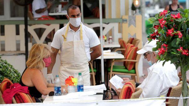 PHOTO: Jeffrey Holinka wears a protective face mask as he waits to receive an order at the On Ocean 7 Cafe along Ocean Drive in Miami Beach, Fla. during the new coronavirus pandemic, May 27, 2020. (Lynne Sladky/AP, FILE)