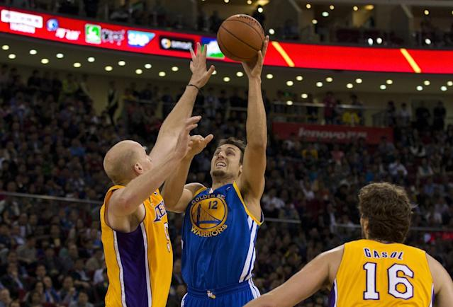 Andrew Bogut of the Golden State Warriors, center, shoots over Chris Kaman of the LA Lakers during their NBA Global Game at the Wukesong Stadium in Beijing Tuesday, Oct. 15, 2013. The Warriors defeated Lakers 100-95. (AP Photo/Andy Wong)