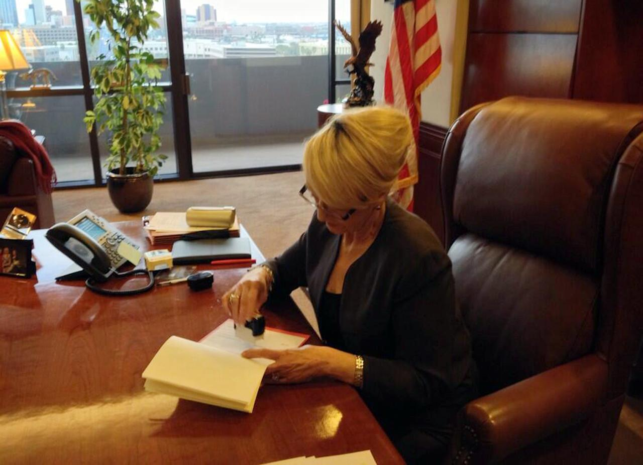 "In this photo tweeted by the office of Arizona Gov. Jan Brewer, Brewer vetoes Senate Bill 1062, a Republican bill that set off a national debate over gay rights, religion and discrimination and subjected Arizona to blistering criticism from major corporations and political leaders from both parties, Wednesday, Feb. 26, 2014, in Phoenix. The caption that accompanied the photo on Twitter read, ""Moments ago, I vetoed #SB1062."" (AP Photo/Office of Arizona Gov. Jan Brewer)"