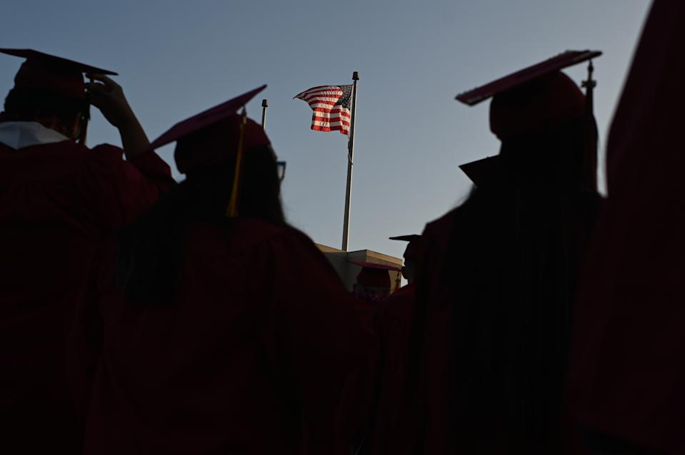"""A US flag flies above a building as students earning degrees at Pasadena City College participate in the graduation ceremony, June 14, 2019, in Pasadena, California. - With 45 million borrowers owing $1.5 trillion, the student debt crisis in the United States has exploded in recent years and has become a key electoral issue in the run-up to the 2020 presidential elections. """"Somebody who graduates from a public university this year is expected to have over $35,000 in student loan debt on average,"""" said Cody Hounanian, program director of Student Debt Crisis, a California NGO that assists students and is fighting for reforms. (Photo by Robyn Beck / AFP)        (Photo credit should read ROBYN BECK/AFP/Getty Images)"""