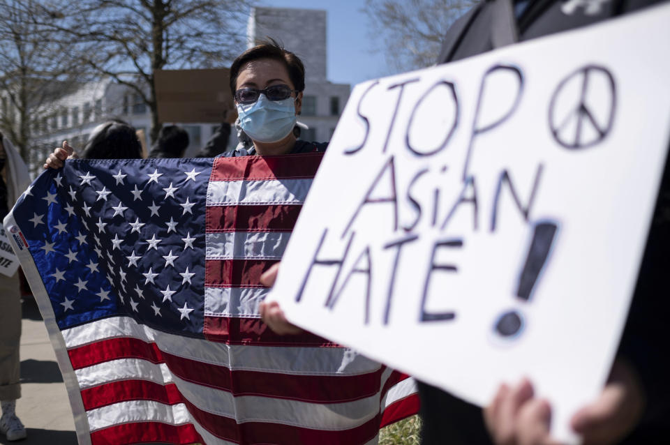 """Lucy Lee, of Marietta, Ga., holds an American flag while rallying outside of the Georgia State Capitol in Atlanta during a unity """"Stop Asian Hate"""" rally Saturday afternoon, March 20, 2021. (AP Photo/Ben Gray)"""