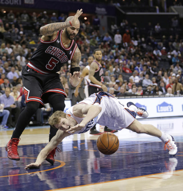 Charlotte Bobcats' Cody Zeller, front, loses the ball as he falls in front of Chicago Bulls' Carlos Boozer during the first half of an NBA basketball game in Charlotte, N.C., Wednesday, April 16, 2014. (AP Photo/Chuck Burton)