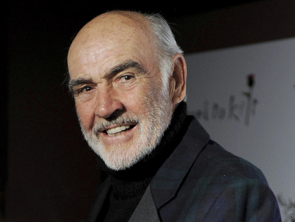 Sean Connery wears a black suit and poses for the camera.