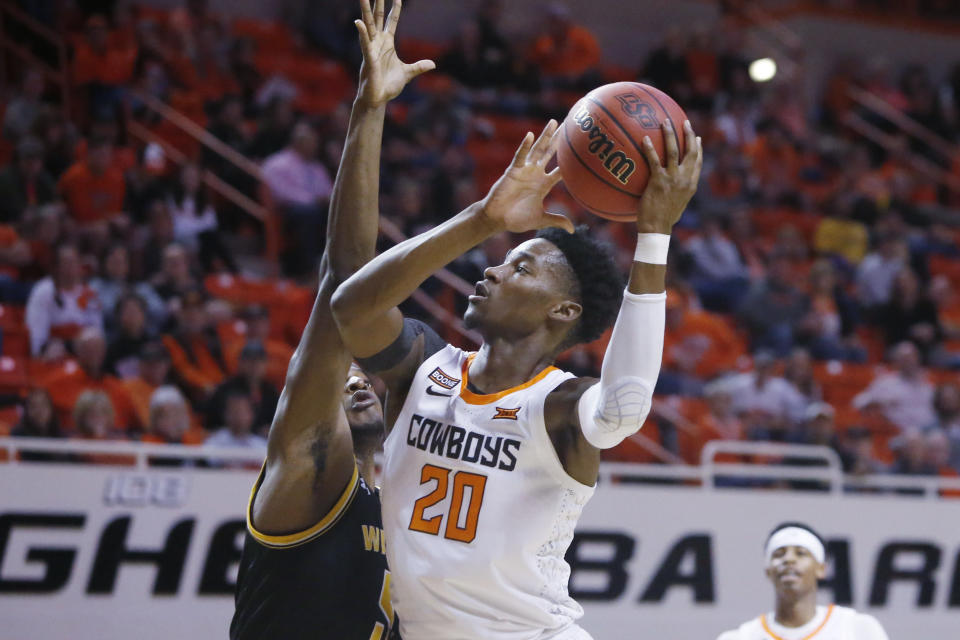 Oklahoma State guard Keylan Boone (20) shoots as Wichita State forward Trey Wade, left, defends, in the first half of an NCAA college basketball game in Stillwater, Okla., Sunday, Dec. 8, 2019. (AP Photo/Sue Ogrocki)