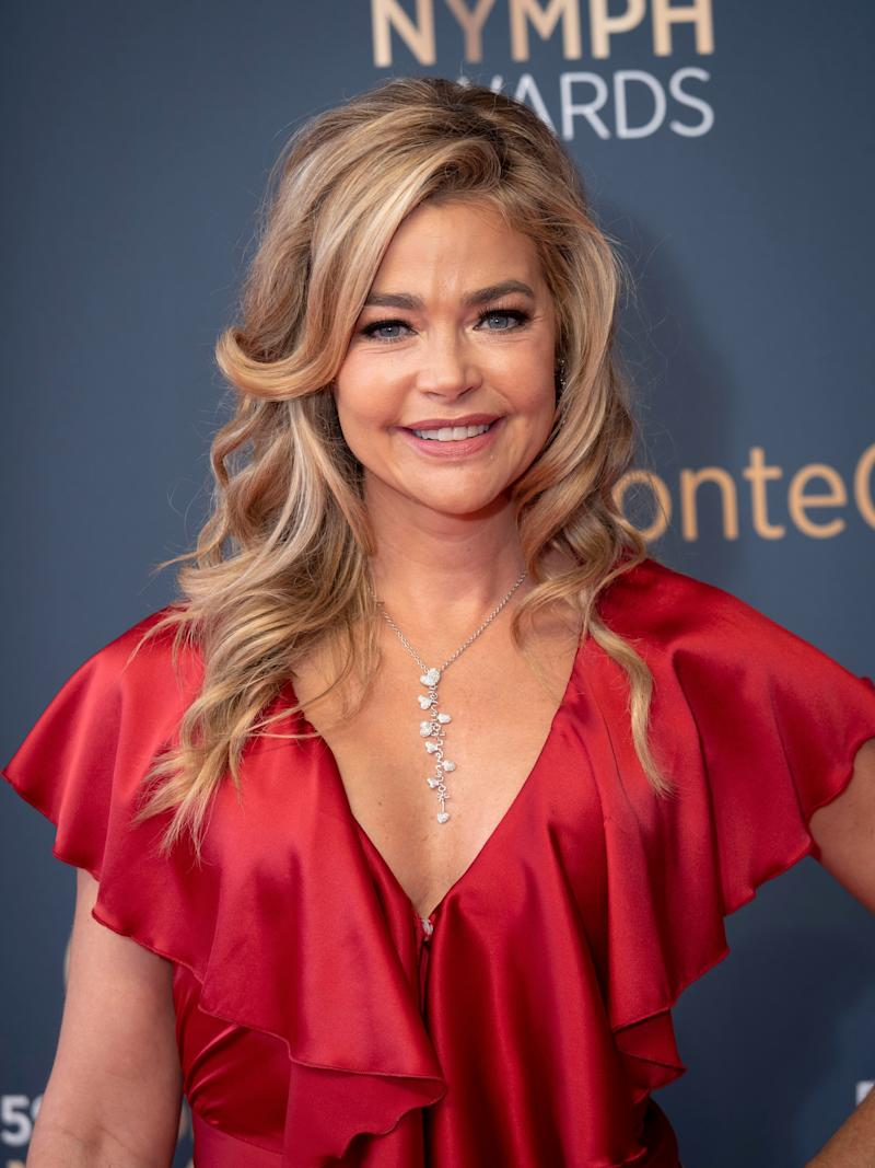Denise Richards poses at the NYMPH Awards wearing a red silk dress