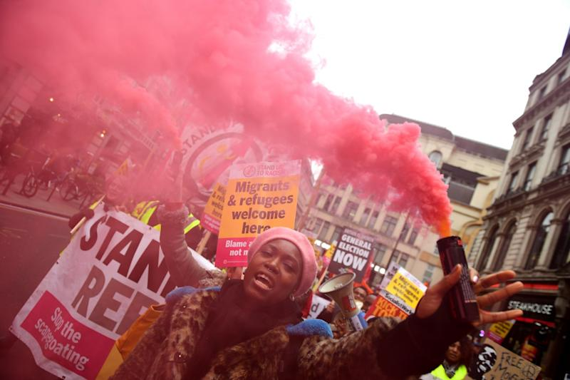 A demonstrator waves a smoke flare as protesters make their way to Westminster (Getty Images)