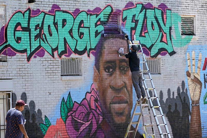 Zack Murray paints a mural honoring George Floyd, on the side of a building in Houston's Third Ward on June 7, 2020. Floyd, who grew up in the Third Ward, died after being restrained by Minneapolis police officers on Memorial Day.