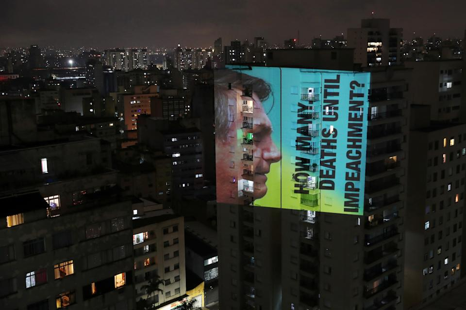 """An image of Brazil's President Jair Bolsonaro with the phrase """"How many deaths until impeachment"""" is projected on a building during a protest against his policies for the coronavirus disease (COVID-19) outbreak and Manaus' health crisis at Santa Cecilia neighbourhood in Sao Paulo, Brazil."""