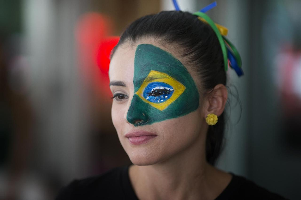 Soccer fan Marcella Guevara, with her face painted, watches televised World Cup soccer action between Brazil and Croatia at the Kukaramakara cafe block party in Miami, Thursday, June 12, 2014. ( AP Photo/J Pat Carter)