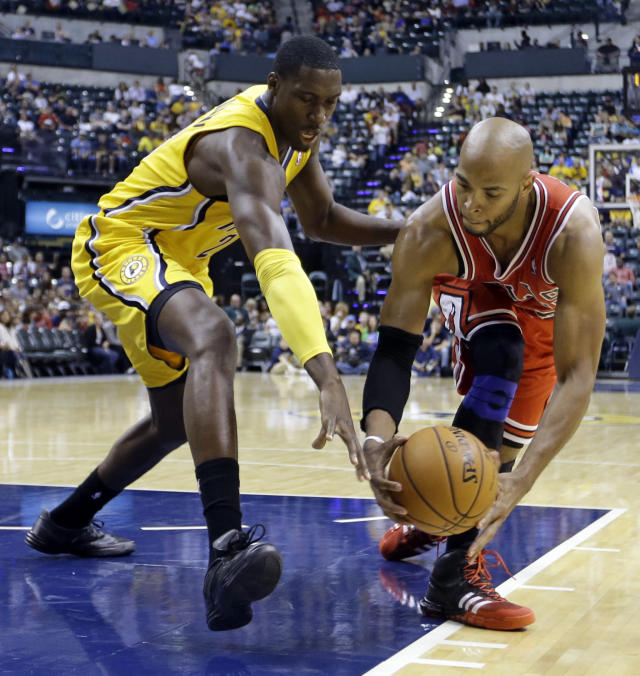 Indiana Pacers center Roy Hibbert, left, attempts to knock the ball away from Chicago Bulls forward Taj Gibson in the first half of an NBA preseason basketball game in Indianapolis, Saturday, Oct. 5, 2013. (AP Photo/Michael Conroy)