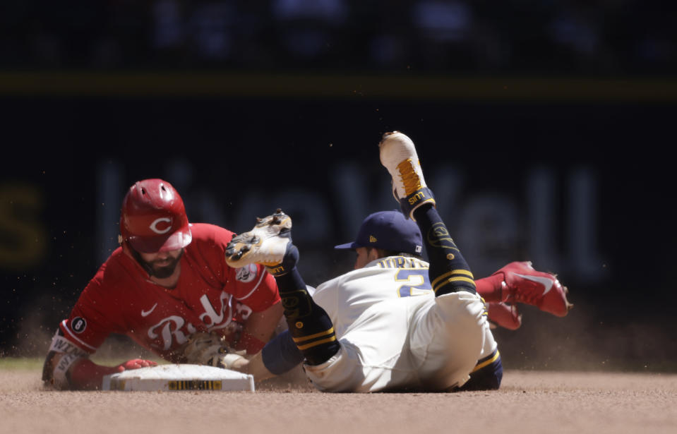Cincinnati Reds right fielder Jesse Winker (33) is tagged out at second base by Milwaukee Brewers third baseman Luis Urias (2) during the sixth inning of a baseball game Wednesday, June 16, 2021, in Milwaukee. (AP Photo/Jeffrey Phelps)
