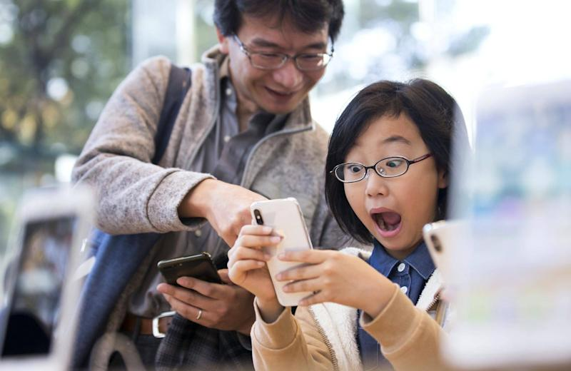 A girl reacts as she tries an iPhone X at the Apple Omotesando store on November 3, 2017 in Tokyo, Japan: Tomohiro Ohsumi/Getty Images