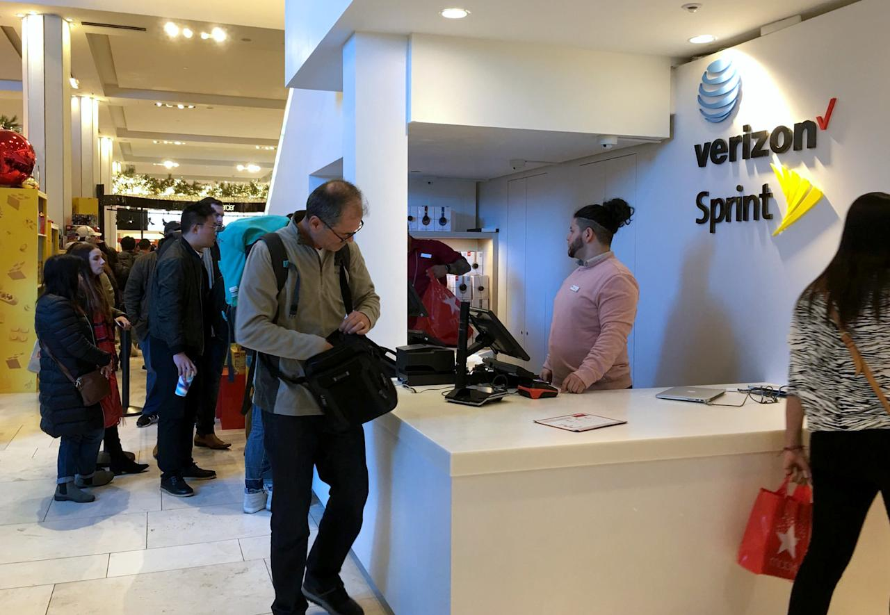 Shoppers wait in line for Apple's iPhone X at Macy's Herald Square store on Thanksgiving Day on Thursday, Nov. 23, 2017, in New York. Shoppers are hitting the stores on Thanksgiving as retailers under pressure look for ways to poach shoppers from their rivals. At Macy's it was the deals like cosmetic and perfume sets from $10 to $20 as well as 40 percent off on boots and shoes that drew attention. (AP Photo/Anne D'Innocenzio)