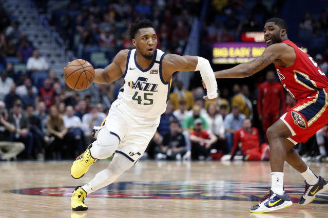 Utah Jazz guard Donovan Mitchell (45) drives to the basket as New Orleans Pelicans guard E'Twaun Moore defends during overtime of an NBA basketball game in New Orleans, Thursday, Jan. 16, 2020. The Pelicans won 138-132. (AP Photo/Gerald Herbert)