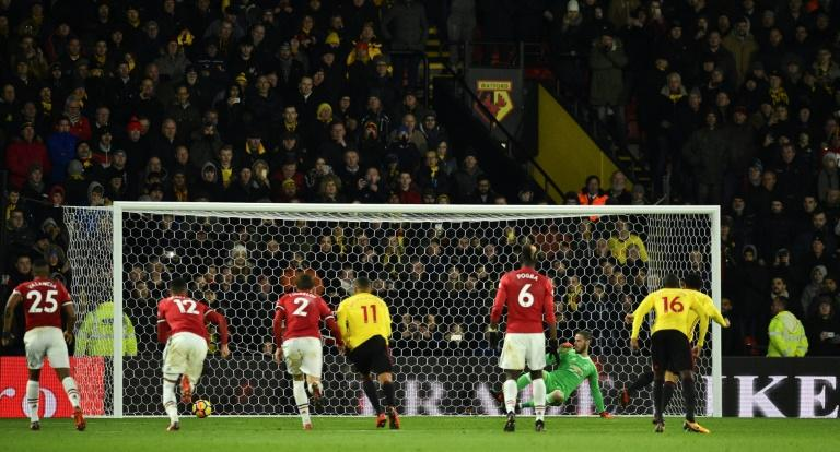Watford striker Troy Deeney (R) scores from the penalty spot against Manchester United on his return from a three-game ban