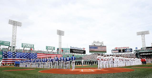 BOSTON, MA - APRIL 20: The Boston Red Sox and the Kansas City Royals stand along the base paths during a pre-game ceremony in honor of the bombings of Marathon Monday before a game at Fenway Park on April 20, 2013 in Boston, Massachusetts. (Photo by Jim Rogash/Getty Images)