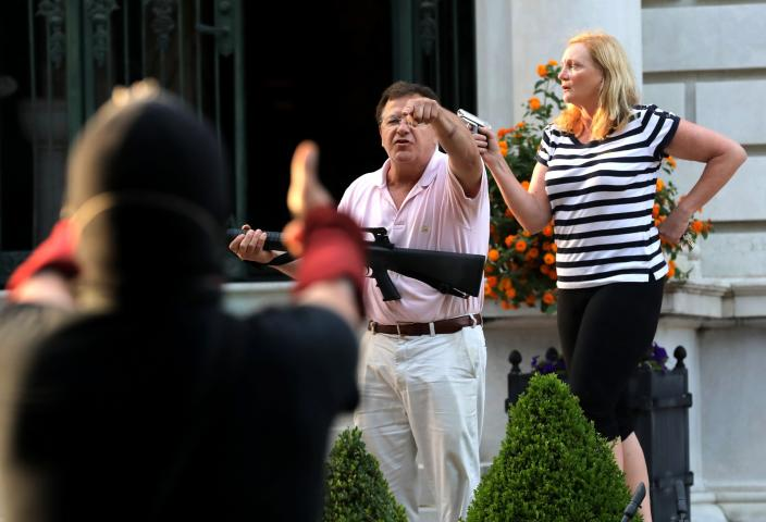 FILE - In this June 28, 2020 file photo, armed homeowners Mark and Patricia McCloskey, standing in front their house along Portland Place confront protesters marching to St. Louis Mayor Lyda Krewson's house in the Central West End of St. Louis. Mark McCloskey, a St. Louis personal injury lawyer who gained national attention after he and his wife waved guns at racial injustice protesters who marched near their home last summer, is on the verge of a 2022 Senate run.(Laurie Skrivan/St. Louis Post-Dispatch via AP, File)