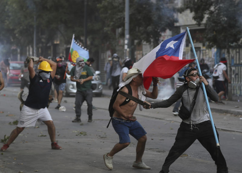 Protesters clash with the police in Santiago, Chile, Friday, Dec. 20, 2019. Chile marks a second full month of unprecedented social revolt that has not only altered the country's political landscape but also prompted a referendum on reforming the country's dictatorship-era. (AP Photo/Fernando Llano)