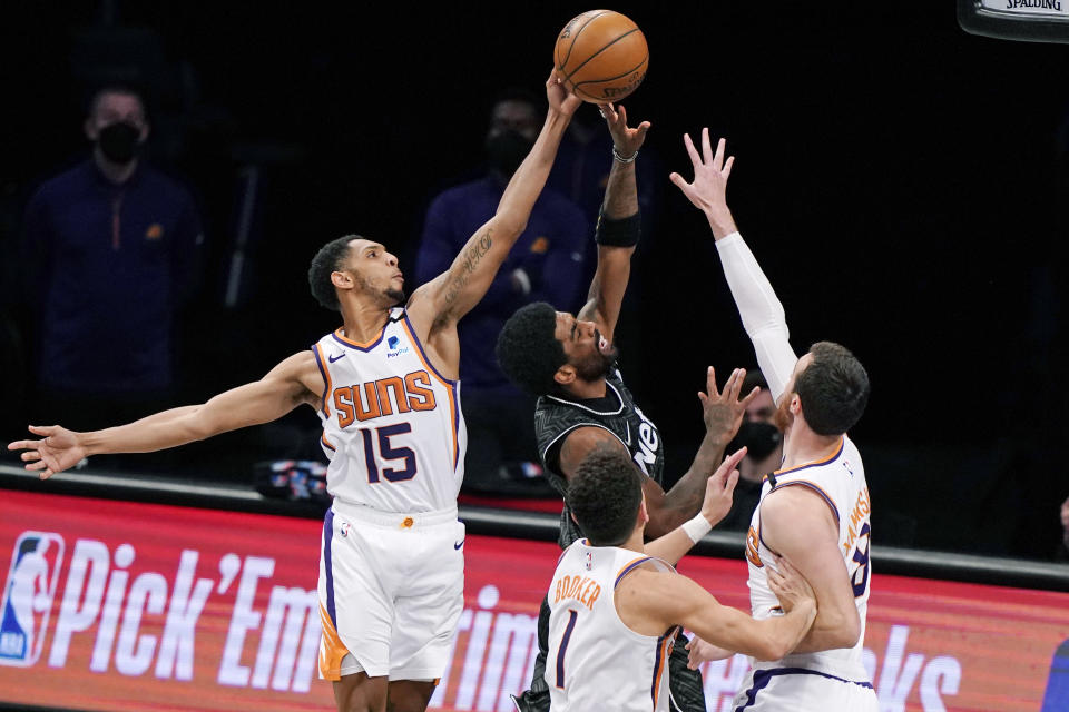 Phoenix Suns guards Cameron Payne (15), and Devin Booker (1) pair up with Suns forward Frank Kaminsky (8) as they triple team Brooklyn Nets guard Kyrie Irving (11) during the second quarter of an NBA basketball game, Sunday, April 25, 2021, in New York. (AP Photo/Kathy Willens)