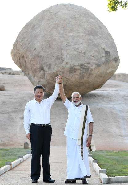 In this Friday, Oct. 11, 2019, handout photo provided by the Indian Prime Minister's Office, Chinese President Xi Jinping and Indian Prime Minister Narendra Modi raise hands together at Arjuna's Penance in Mamallapuram, India. Xi on Friday met with Modi at a time of tensions over Beijing's support for Pakistan in opposing India's downgrading of Kashmir's semi-autonomy and continuing restrictions on the disputed region. (Indian Prime Minister's Office via AP)