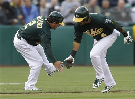 Oakland Athletics' Coco Crisp, right, is congratulated by third base coach Mike Gallego (2) after Crisp hit a home run off New York Yankees CC Sabathia in the first inning of a baseball game Tuesday, June 11, 2013, in Oakland, Calif. (AP Photo/Ben Margot)
