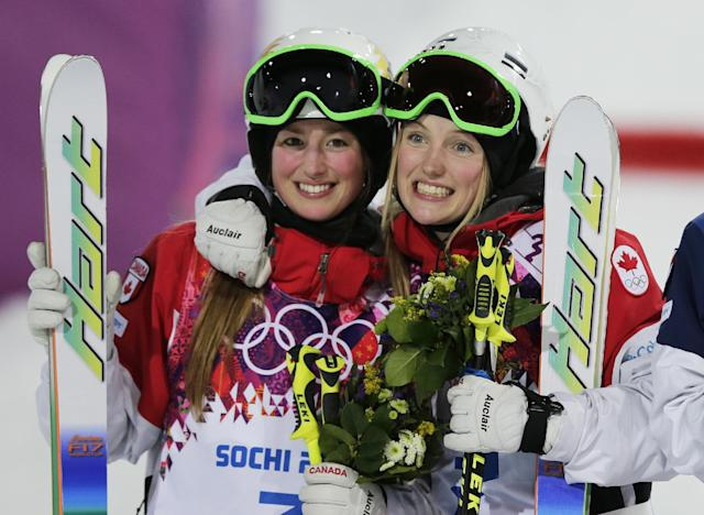 Canada's Justine Dufour-Lapointe, right, celebrates her gold medal in the women's moguls final, with her sister and silver medalist Chloe Dufour-Lapointe, left, at the Rosa Khutor Extreme Park, at the 2014 Winter Olympics, Saturday, Feb. 8, 2014, in Krasnaya Polyana, Russia. (AP Photo/Andy Wong)