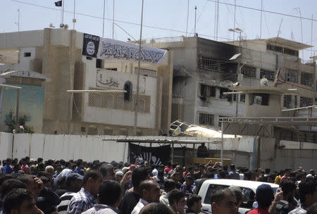 Residents gather at governorate building of Nineveh province after the predominantly Sunni militants from the radical Islamic State of Iraq and the Levant (ISIL) took control in the city of Mosul
