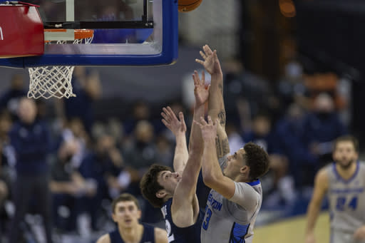 Creighton forward Christian Bishop (13) makes a shot over Xavier forward Zach Freemantle (32) in the second half during an NCAA college basketball game on Wednesday, Dec. 23, 2020, in Omaha, Neb. (AP Photo/John Peterson)