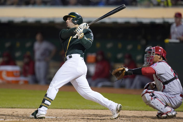 Oakland Athletics' Ramon Laureano, left, watches his three-run home run in front of Los Angeles Angels catcher Kurt Suzuki during the seventh inning of a baseball game in Oakland, Calif., Monday, July 19, 2021. (AP Photo/Jeff Chiu)