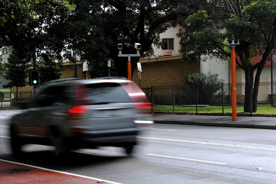 Picture of a car speeding by a speed camera in Sydney.