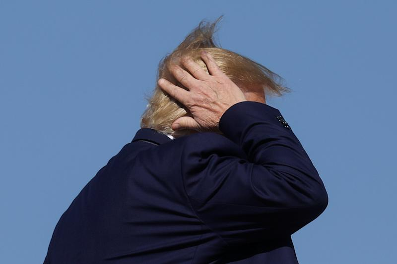 President Donald Trump holds on his hair as he boards Air Force One to depart Washington for travel to Pennsylvania from Joint Base Andrews, Maryland, U.S., October 23, 2019. REUTERS/Leah Millis