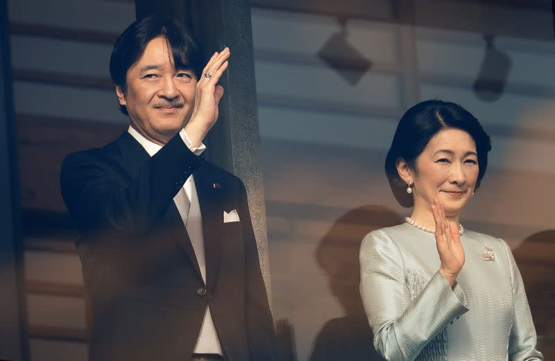 Crown Prince Akishino and Crown Princess Kiko wave to well-wishers during a public appearance for New Year celebrations at the Imperial Palace in Tokyo