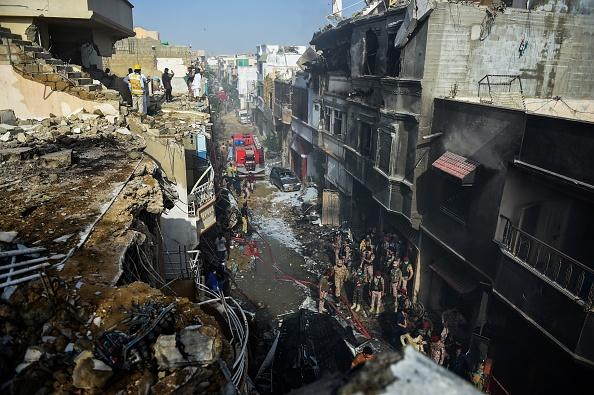 Rescue workers gather at the site after a Pakistan International Airlines aircraft crashed in a residential area in Karachi.