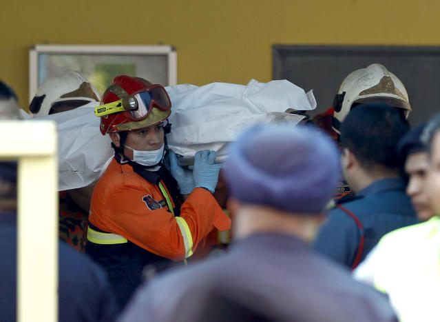 <p>The body of a victim is carried out by rescue personnel from an Islamic religious school after a fire on the outskirts of Kuala Lumpur Thursday, Sept. 14, 2017. (Photo: Daniel Chan/AP) </p>
