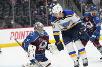 St. Louis Blues center Brayden Schenn, right, jumps in the air to avoid a shot as Colorado Avalanche goaltender Philipp Grubauer covers the net in the third period of Game 1 of an NHL hockey Stanley Cup first-round playoff series Monday, May 17, 2021, in Denver. Colorado won 4-1. (AP Photo/David Zalubowski)