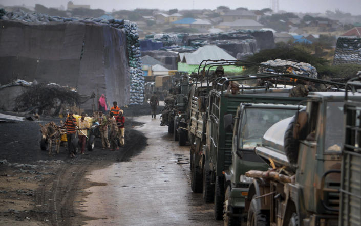 In this photo released by the African Union-United Nations Information Support Team, Somali youths pull a donkey-drawn water cart, left, while a convoy of Kenyan soldiers serving with the African Union Mission in Somalia (AMISOM) passes by, right, in Kismayo, southern Somalia, Tuesday, Oct. 2, 2012. Allied African troops have taken full control of Kismayo in Somalia, the last stronghold of al-Shabab Islamist rebels who have been fighting against the country's internationally backed government, a Kenyan military official said Tuesday, and Kenya Defence Forces and the Somali National Army are now patrolling the streets. (AP Photo/AU-UN IST, Stuart Price)