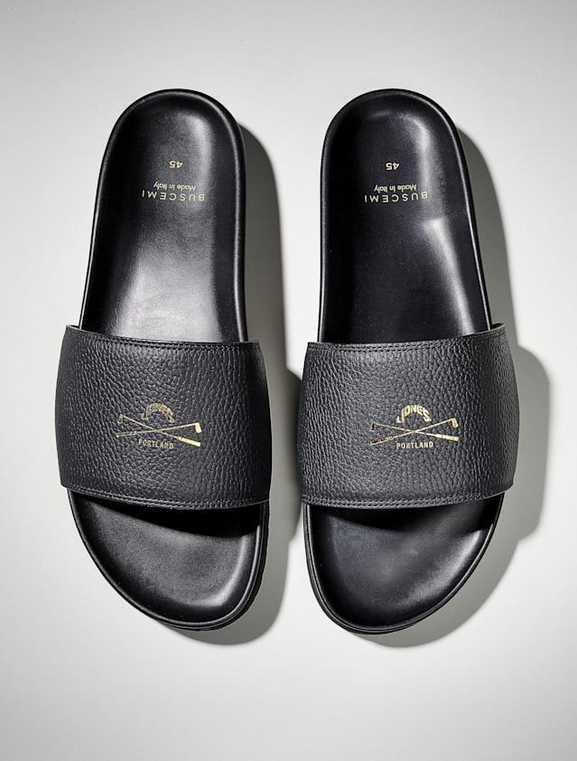 "Handmade in Italy, these limited-edition slides offer the simple elegance your feet deserve after 18 holes. <a href=""https://www.jonessportsco.com/products/jones-x-buscemi-slide?variant=13106551685173"" rel=""nofollow noopener"" target=""_blank"" data-ylk=""slk:Available at jonessportsco.com"" class=""link rapid-noclick-resp""><em>Available at jonessportsco.com</em></a><br> <a href=""https://trendygolfusa.com/products/jones-golf-bags-le-jones-x-buscemi-slides-navy-2019??utm_source=GOLFDIGESTEOTC&utm_medium=Referral&utm_campaign=2019DIGEST"" rel=""nofollow noopener"" target=""_blank"" data-ylk=""slk:BUY NOW: $200"" class=""link rapid-noclick-resp""><strong>BUY NOW</strong>: $200</a>"
